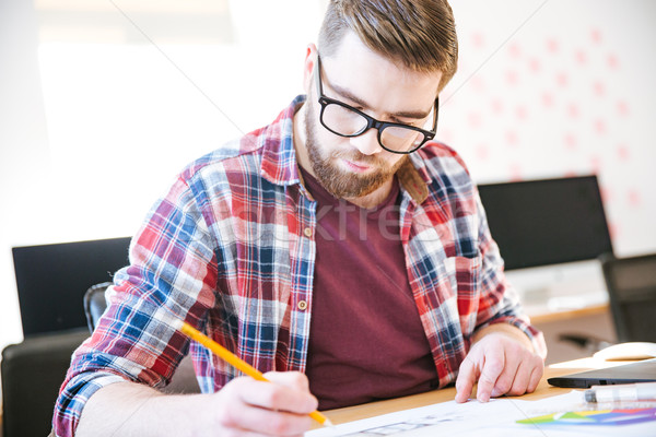 Concentrated young man making sketches with pencil  Stock photo © deandrobot