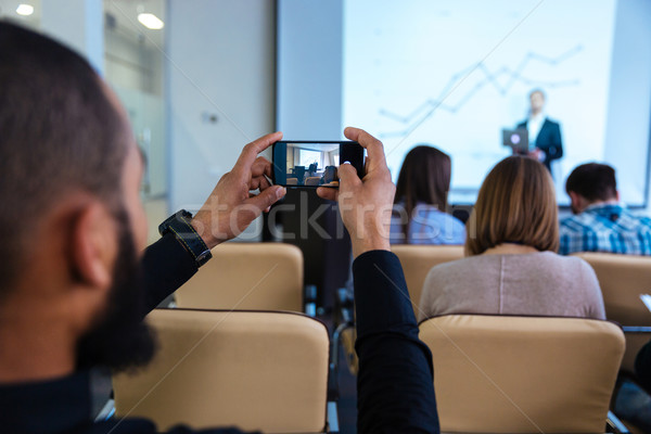 Young man making video with smartphone on business conference Stock photo © deandrobot