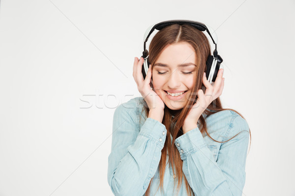 Happy woman in earphones listening to musinc with closed eyes  Stock photo © deandrobot