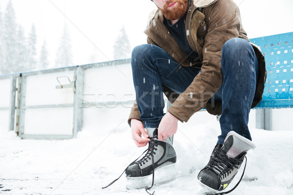 Man tying shoelace on ice skates outdoors Stock photo © deandrobot