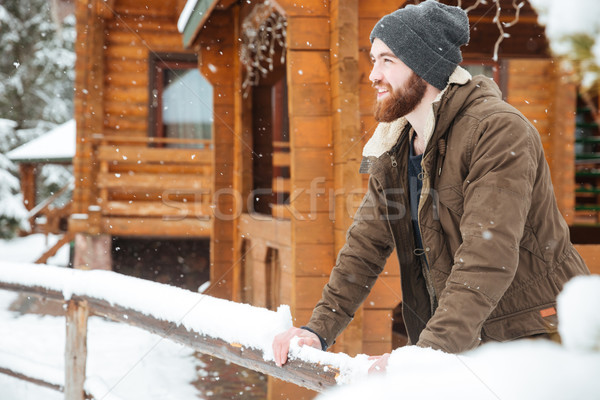 Smiling bearded man standing near wooden cottage in winter  Stock photo © deandrobot