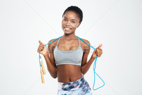 Smiling afro american woman holding skipping rope Stock photo © deandrobot