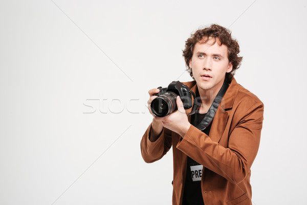 Male reporter holding camera Stock photo © deandrobot