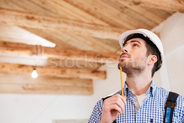 Close-up portrait of a builder examining his working place Stock photo © deandrobot