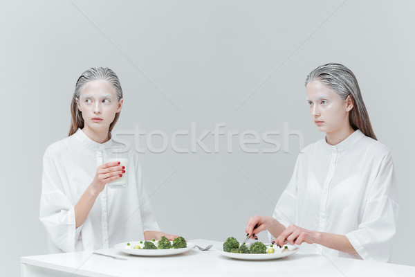 Two women eating at the table Stock photo © deandrobot