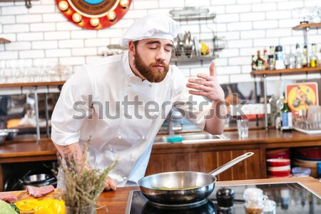 Funny young chef cook covered his face with frying pan Stock photo © deandrobot
