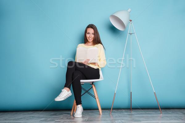 Sorridente mulher bonita olhando câmera livro Foto stock © deandrobot