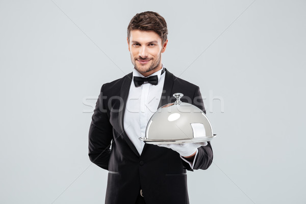 Smiling young butler holding tray with silver catering dome Stock photo © deandrobot