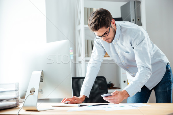 Businessman working with computer and using cell phone in office Stock photo © deandrobot