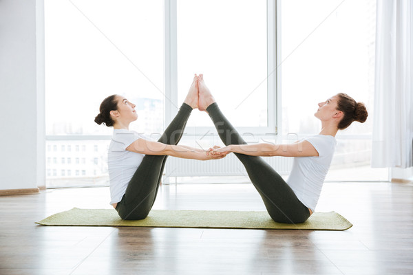 Two women stretching legs on green yoga mat Stock photo © deandrobot