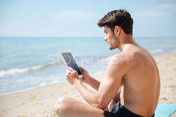 Сток-фото: красивый · мужчина · экране · таблетка · пляж · серьезный · красивый