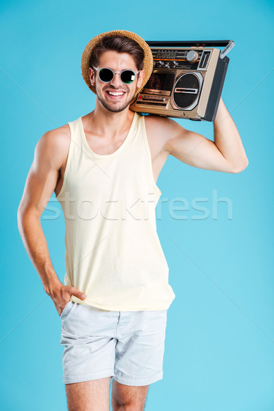 Cheerful attractive young man in hat and sunglasses holding boombox Stock photo © deandrobot