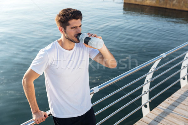 Stock photo: Sportsman standing on wooden terrace near sea and drinking water