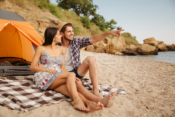 Man pointing at something while sitting with girlfriend on beach Stock photo © deandrobot