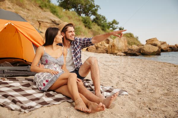Uomo punta qualcosa seduta fidanzata spiaggia Foto d'archivio © deandrobot
