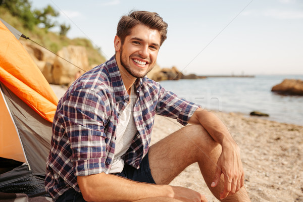Smiling man tourist sitting in touristic tent at the beach Stock photo © deandrobot