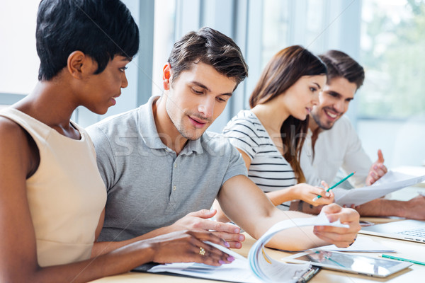 Serious young people sitting and creating business plan in office Stock photo © deandrobot