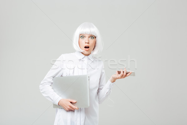 Amazed shocked young woman holding laptop and cell phone Stock photo © deandrobot