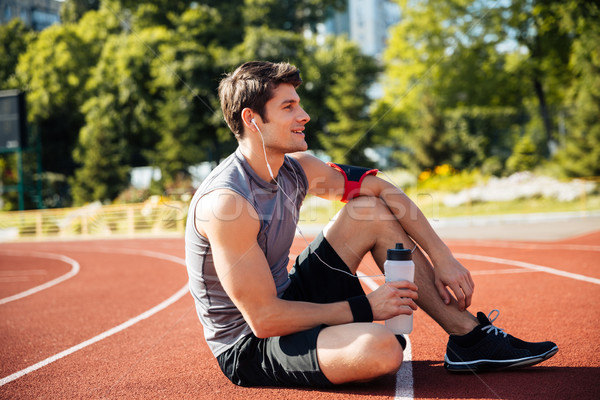 Young handsome man athlete resting at the stadium Stock photo © deandrobot