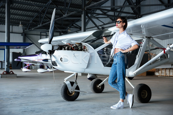 Attractive young woman in sunglasses standing near small aircraft Stock photo © deandrobot