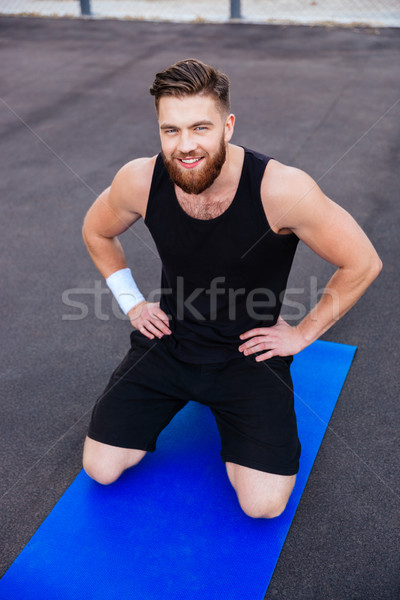 Happy smiling fitness man doing workout on blue mat outdoors Stock photo © deandrobot