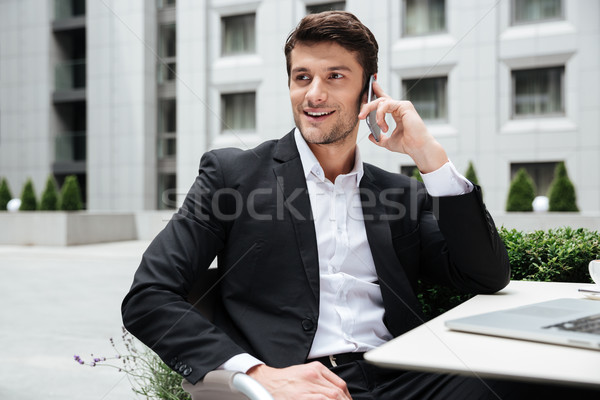 Cheerful young businessman talking on cell phone in outdoor cafe Stock photo © deandrobot