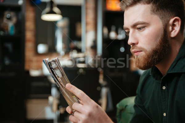 Young man at barbershop reading magazine. Stock photo © deandrobot