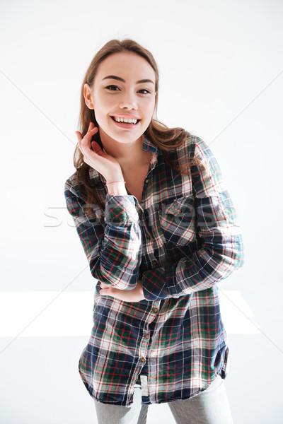 Derűs bájos fiatal nő kockás póló pózol Stock fotó © deandrobot