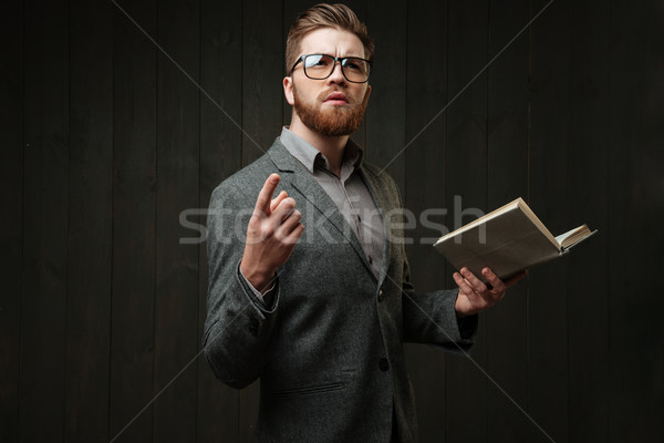 Young bearded man in eyeglasses and casual suit learning script Stock photo © deandrobot
