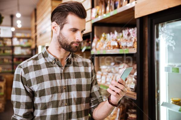 Guapo barbado joven teléfono celular comestibles tienda Foto stock © deandrobot