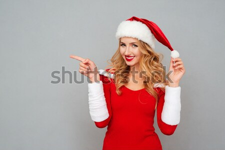 Woman in dress and Santa's hat shows the finger Stock photo © deandrobot