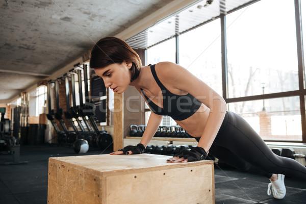 Sportswoman doing pushups in gym Stock photo © deandrobot