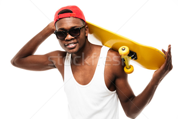Happy african young man in cap and sunglasses with skateboard Stock photo © deandrobot