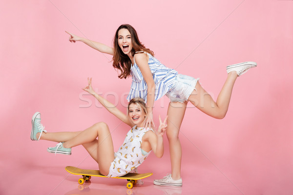 два женщины скейтборде указывая далеко Сток-фото © deandrobot