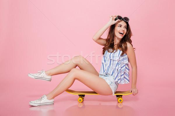 счастливым привлекательный Солнцезащитные очки сидят скейтборде Сток-фото © deandrobot