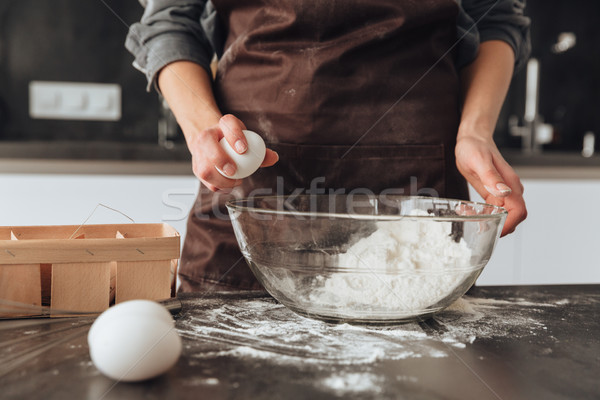 Cropped photo of young woman cooking the dough. Stock photo © deandrobot