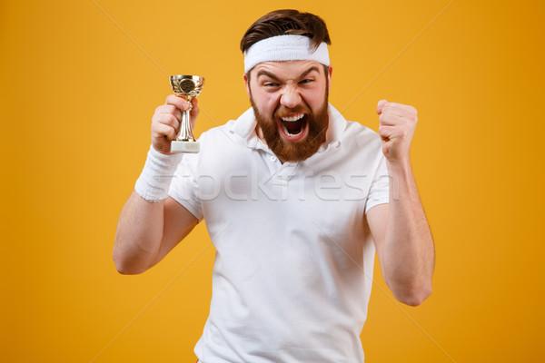 Emotional young sportsman holding reward make winner gesture. Stock photo © deandrobot