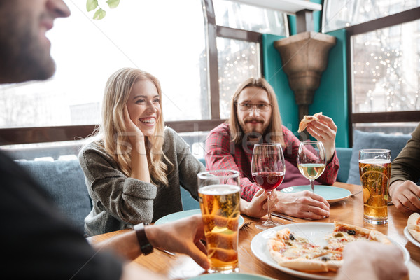 Stock photo: Young happy friends in cafe eating pizza while drinking alcohol.