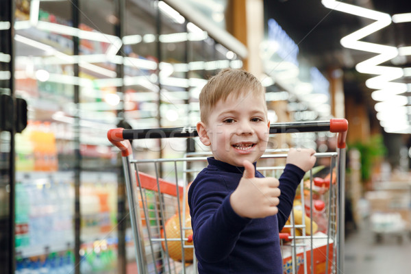 Happy boy near shopping trolley showing thumb up  Stock photo © deandrobot