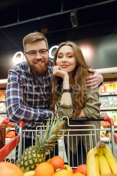 Attractive Loving couple standing near the shopping trolley Stock photo © deandrobot