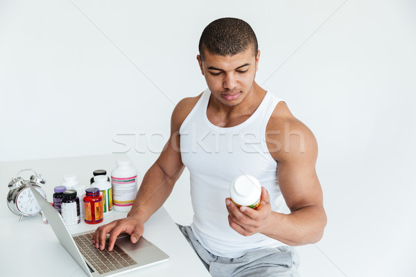 Handsome young sportsman holding sport nutrition and using laptop computer Stock photo © deandrobot