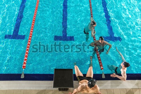 Rear view of three male swimmers diving into a pool Stock photo © deandrobot