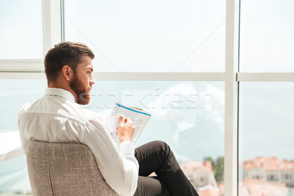 Back view of bearded man in business clothes reading journal Stock photo © deandrobot