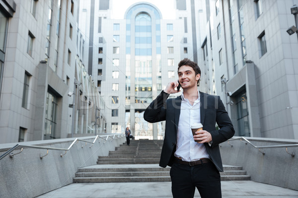 Businessman holding coffee and phone Stock photo © deandrobot