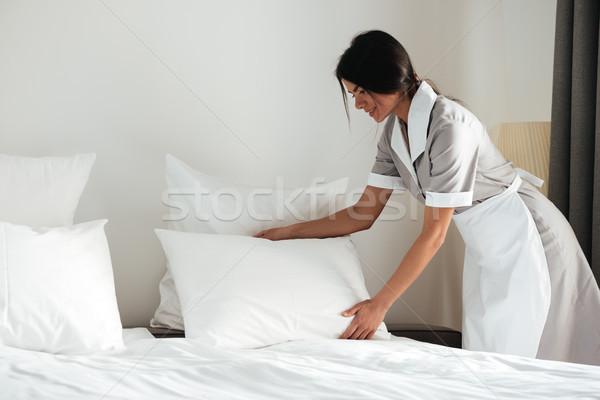Genç otel hizmetçi yukarı yastık yatak Stok fotoğraf © deandrobot