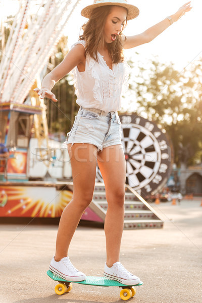 Young woman with skateboard outdoors. Looking aside. Stock photo © deandrobot