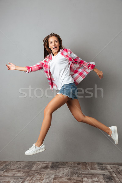 Full-length photo of emotional jumping girl in casual wear Stock photo © deandrobot