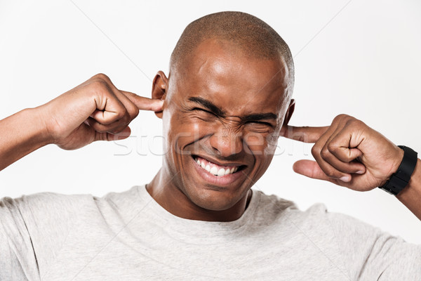 Displeased african man closes ears from a noise. Stock photo © deandrobot