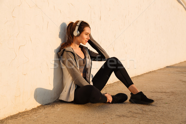 Portrait of cheerful young sport woman listening to music, resti Stock photo © deandrobot