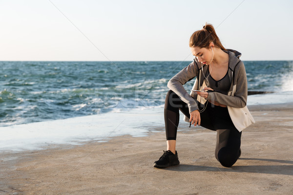 Photo of young healthy sport woman sitting on knee, checking mes Stock photo © deandrobot
